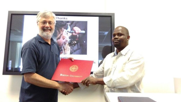 Dr. John Wasige receiving this recognition certificate upon completion of the GIS Course